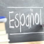 """Hand writing on a blackboard in a language class with the word """"Spanish"""" written on it. Some books and school materials."""